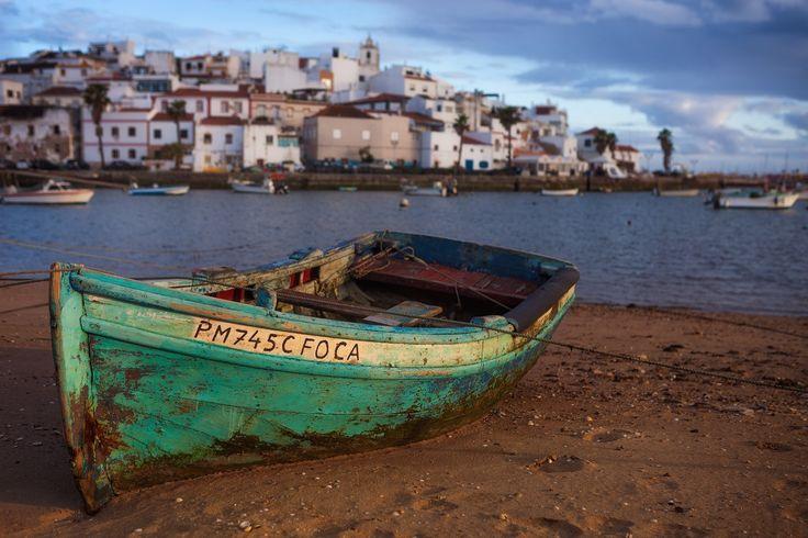 Old Fishing Boat - An old colorful row boat sits on the shore of a small town in southern Portugal.