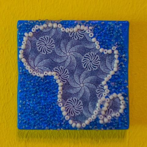 Shop: Canvas D'Afrique - Blue Swirls. This Africa is partially beaded on canvas in light blue and white with a center of varying blue patterned fabrics. Size: 10cm x 10cm. By Beadoir D'Afrique