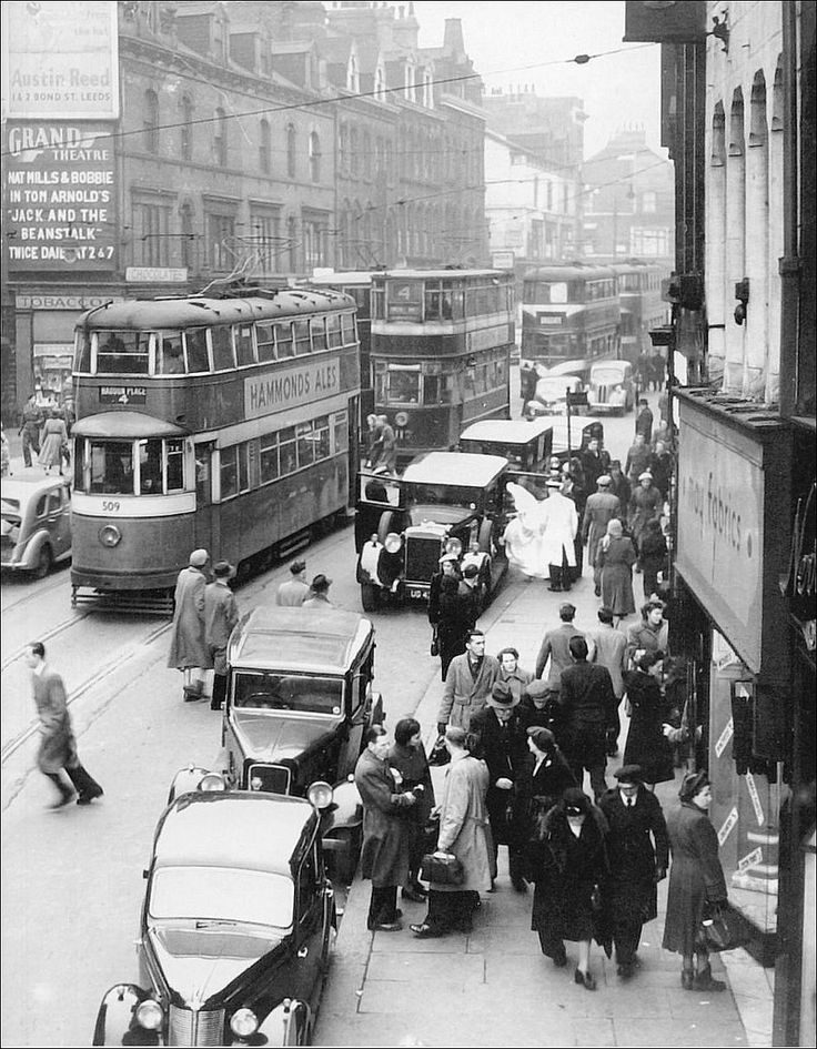 https://flic.kr/p/8kLhxM | Leeds: Upper Briggate. 1951. | Lots going on here in this photograph including a Pantomime and a Wedding, rumour has it, the bride walked straight through the car and got on the tram.