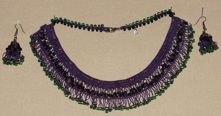 Mor dantel ipi kullanılarak yeşil cam boncuk ve siyah kum boncuklar kullanılarak örülmüştür.
