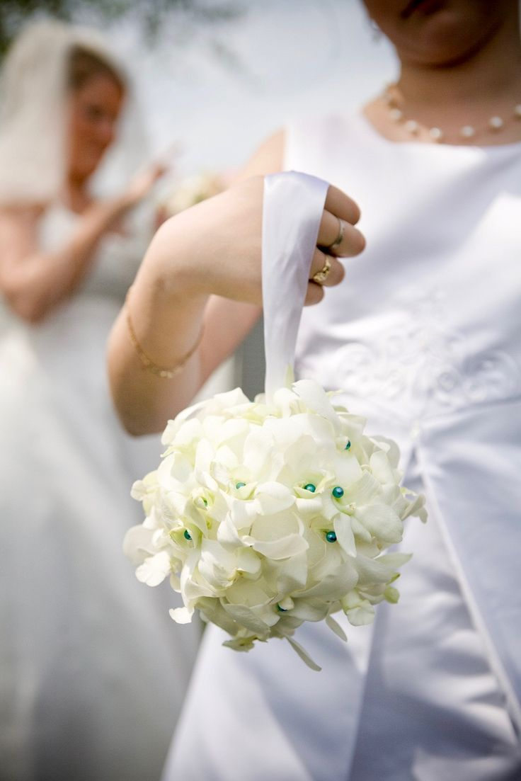 The flower girl carrying a ball of delicate white orchids with an accent in the wedding palette at DuPont Country Club. Mike Kehr Photography.