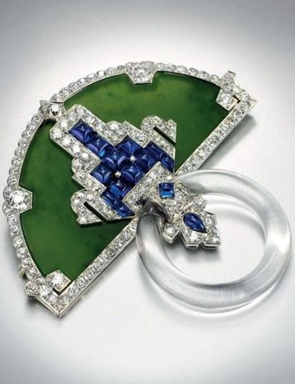 Cartier brooch designed as a half-moon shaped carved jadeite plaque, set with cabochon sapphires, trimmed with Old European, circular and single-cut diamonds, suspending an articulated carved rock crystal hoop, mounted in platinum, circa 1925.