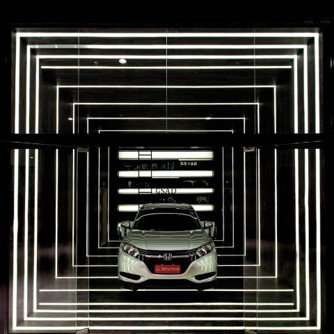 Garagem - Adriano Stancati e Daniele Guardini - A grande caixa revestida de amadeirado preto e cinza foi rasgada por anéis de luz, espaçados de maneira progressiva, entre o futurismo e o minimalismo. Observe ainda a estante na parede de fundo, composta de uma tela tensionada retroiluminada.