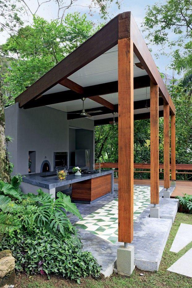 A cozinha da área externa tem bancada de ardósia e ladrilhos hidráulicos paginados pela arquiteta Ligia Cury – vaso decerâmica de Kimi Nii