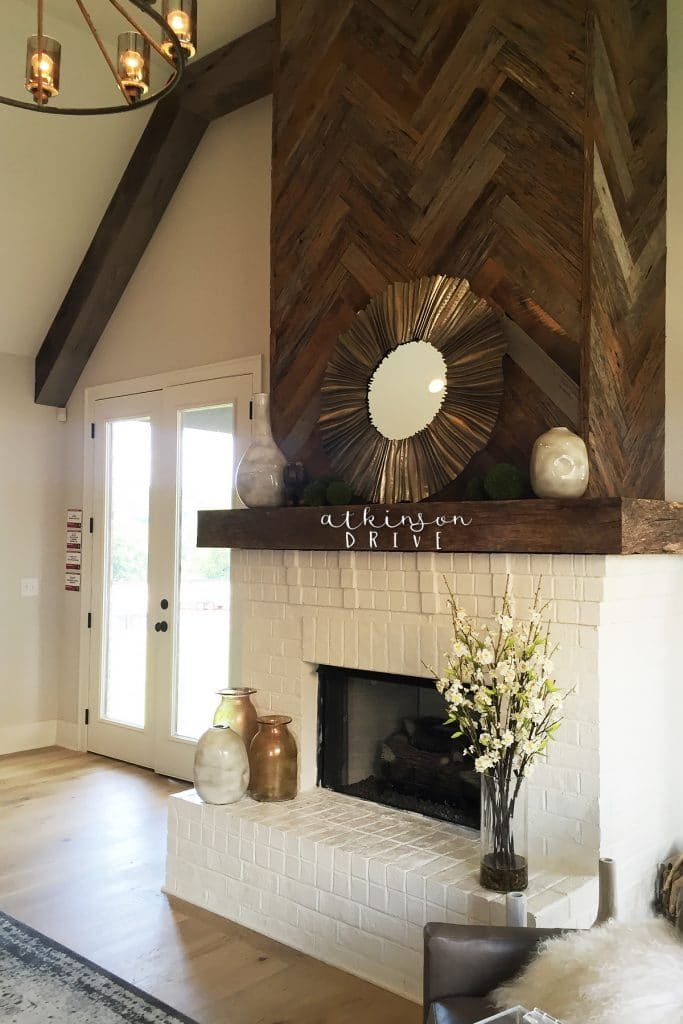 White painted brick fireplace with a herringbone wood feature above.