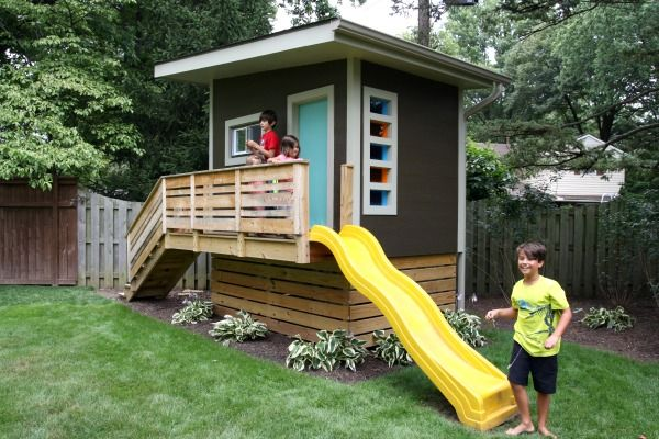 Raised playhouse with storage for large outside toys hidden by wooden slats from the front and sides: modern playhouse 5