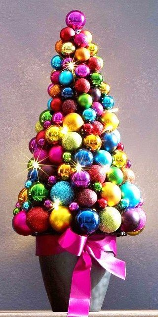 Christmas tree made with a rainbow of Christmas ornaments.                                                                                                                                                                                 More