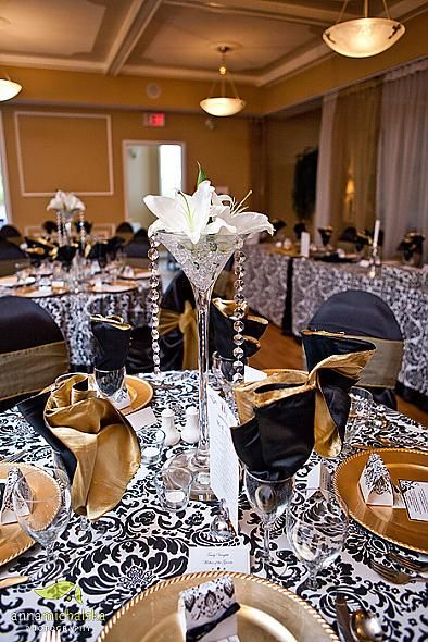 Use Ivory and black damask tablecloths, gold chargers, gold napkins, black chair covers, gold chair sash