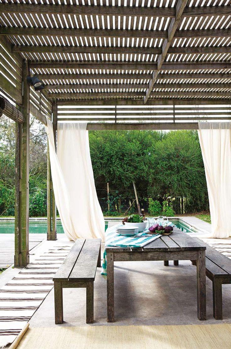 Pérgola de madera con cortinas claras, mesa de madera y alfombra corrida en jardín con pileta. Espacio aireado y fresco en una casa con acento en las texturas.