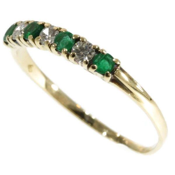 Anillo de oro con esmeraldas y diamantes talla brillante en engaste en línea abierto, fechado en 1980