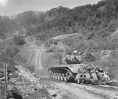 US Marines crouching behind a M26 Pershing tank, near Hongcheon, Korea, 22 May 1951. http://wrhstol.com/2yEXMQX