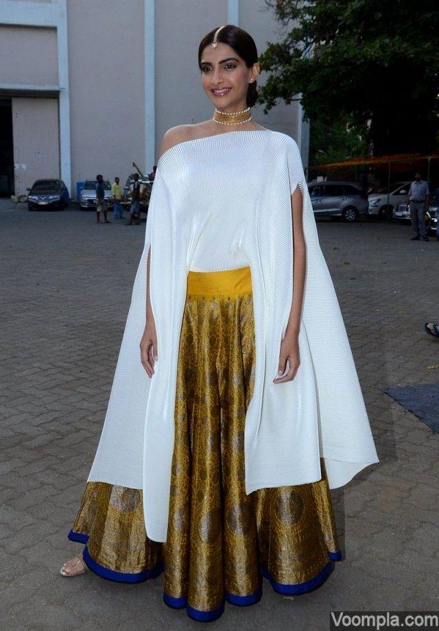 Sonam Kapoor style Payal Khandwala gold lehenga white poncho
