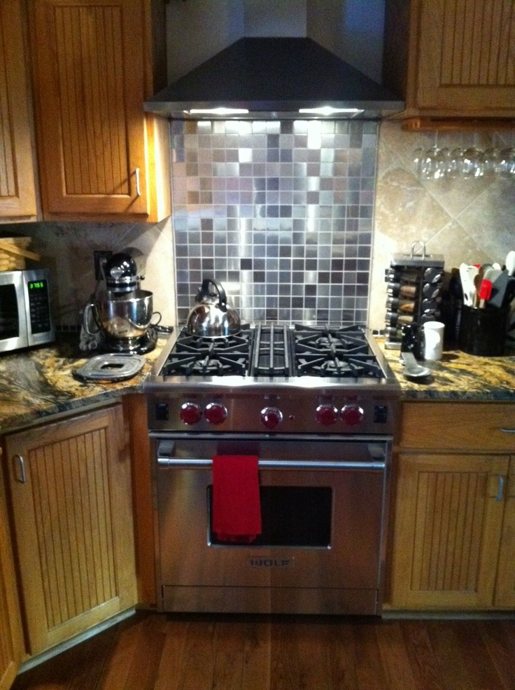 new wolf range with 2x2 inch stainless steel tile backsplash and hood