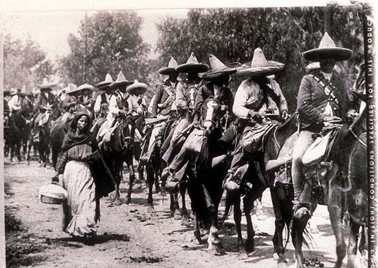 Mexico, Revolution, Photo of a woman walking next to a line of mounted Zapatista. Photo by Agustín Victor Casasola (1874-1938). Cf. http://content.cdlib.org/ark:/13030/hb1p300718/?layout=metadata=calisphere