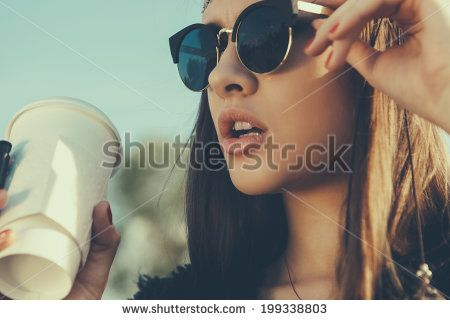 Pretty hipster girl in sunglasses with cup of coffee. Close-up lifestyle outdoor portrait - stock photo