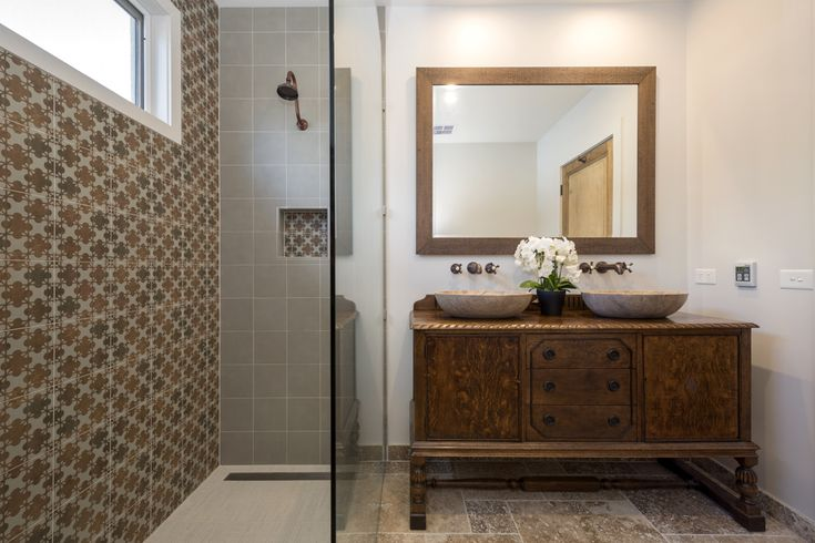 This family bathroom exudes character. An antique buffet has been repurposed as a vanity unit. Keeping a Mediterranean feeling, the warm browns and oranges have been reflected in the wall tile in the shower, and complimented by antique brass fittings.