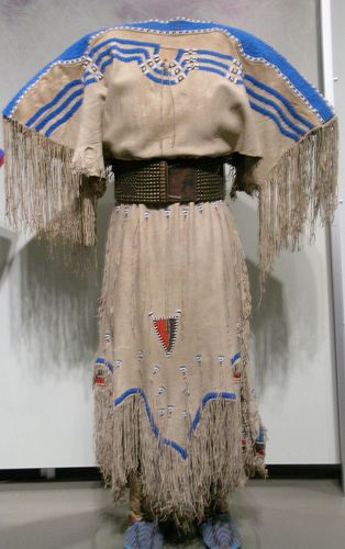 Piegan (Blackfoot) Two Hide Dress.    Circa 1850, Canada. With belt (1890) and moccasins (1880.) Dress made of hide, red and blue wool, pony beads and sinew. Belt made of harness leather, brass tacks and sinew. Moccasins made of hide, seed beads, cloth, rawhide, canvas, sinew and thread.