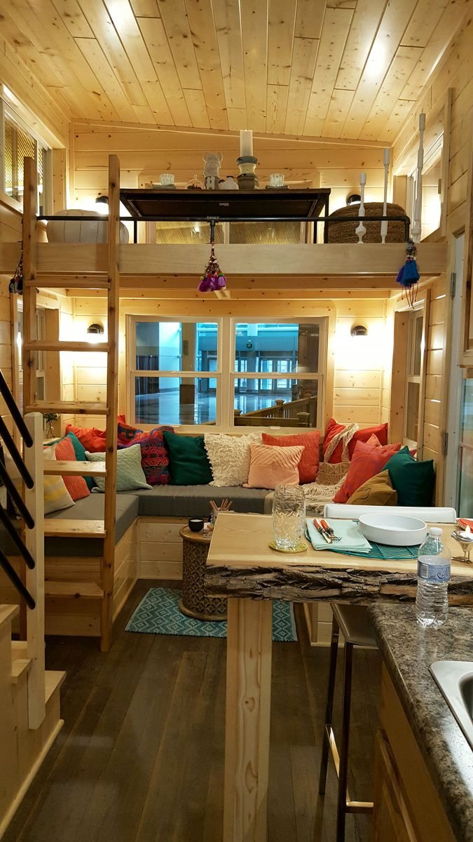 The tiny house includes a U-shaped sofa in the living room with a loft overhead. The loft can be used as a second lounging area, for sleeping, or for storage.