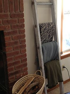 Old ladder used to hang extra blankets (or scarves) both practical and decorative.