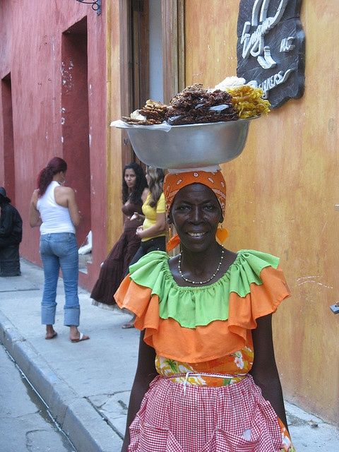 One of the pictures that everyone wants to take when traveling to Cartagena. This Afrocolombian woman is wearing very traditional clothes of Colombia and selling fruits. #travelandmakeadifference #palenquetourscolombia #Cartagena #ColonialVillage
