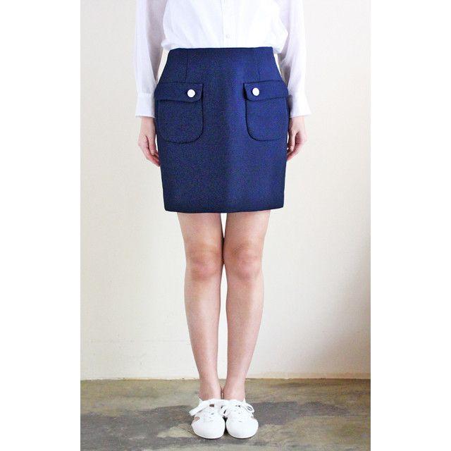 フラップポケットが可愛いミンスパイのスカート。上品なネイビーブルーに、シルバーのボタンがつけられています。