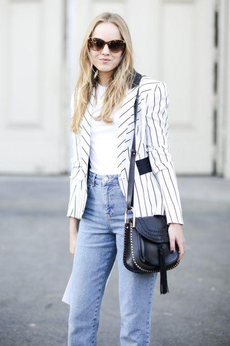 Młoda kobieta w białej marynarce w paski, jasnych jeansach i z czarną torebką typu listonoszka.
