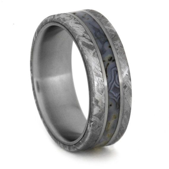 When picking out the perfect ring you want to find something that is unique and special. This titanium ring is exactly that. The meteorite edges have been etched with acid to reveal the characteristic Widmanstatten pattern. No two pieces are ever exactly the same. In the center, between two titanium pinstripes, lies entrancing dinosaur bone!  The dinosaur bone displays the amazing cell structure visible in elevates the beauty and character of this ring. This structure shows up as honeycomb…