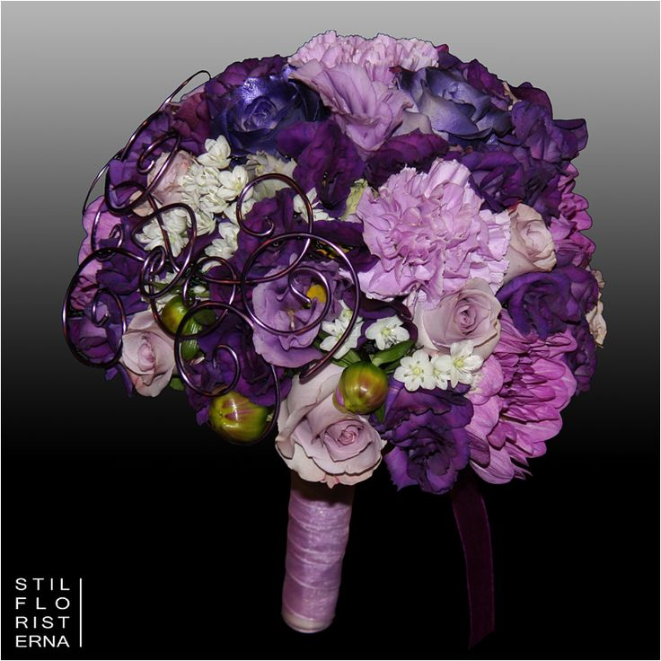 Elegant och lyxig brudbukett i hållare i olika lila toner, med detaljarbeten i lila tråd.