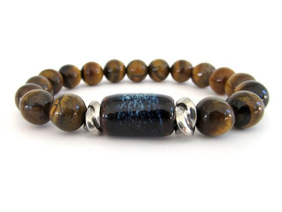 Men's stretch bracelet with 10mm Tiger Eye beads, a ceramic focal bead and pewter twist accent beads. A masculine men's bracelet that is neutral enough to wear every day. The ceramic focal bead has hues of blue and brown blending together giving the bracelet a cool, hip vibe.