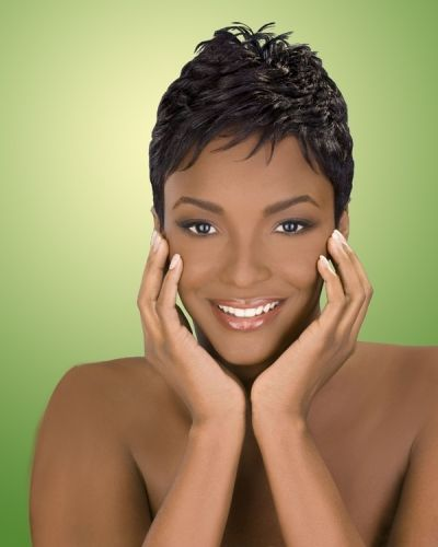 Naturally wavy hair is cut very short and styled to have it bring out the best in the pixie look. The natural springy, bouncy texture of African-American hair is tempered by a very short crop, and slicked down in a wet finish that defines locks, yet keeps them close to the scalp. A bit of a fade is done from the crown to the sides, as hair on top is cut longer and at an angle, so that a steeper-than-usual curve is observed going down. The hairline on the forehead follows the curve as well…