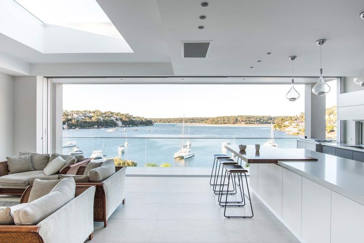 Modern Waterfront home in Sydney | Modern Home | Contemporary house | Sydney architecture | beach house | modern interior | white minimalist design | partition wall | glass sliding doors | designer table | designer chairs | dining room | modern kitchen | white bench top | butlers pantry | view | bay |
