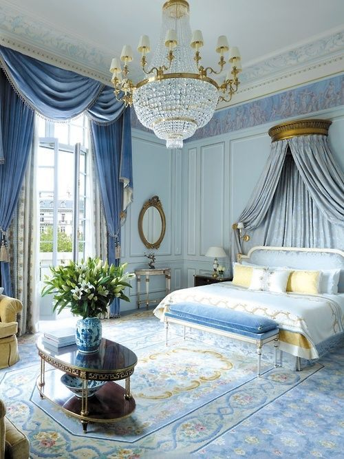 Stunning formal Parisian bedroom with a canopy bed, gold and crystal chandelier, crown mouldings and floor-to-ceiling silk drapes, all decked out in shades of French blue. #luxurybedroom