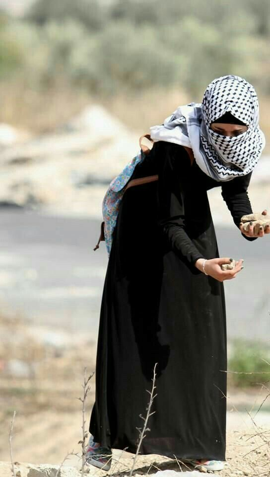 Palestinian woman gathering rocks to attack Israelis