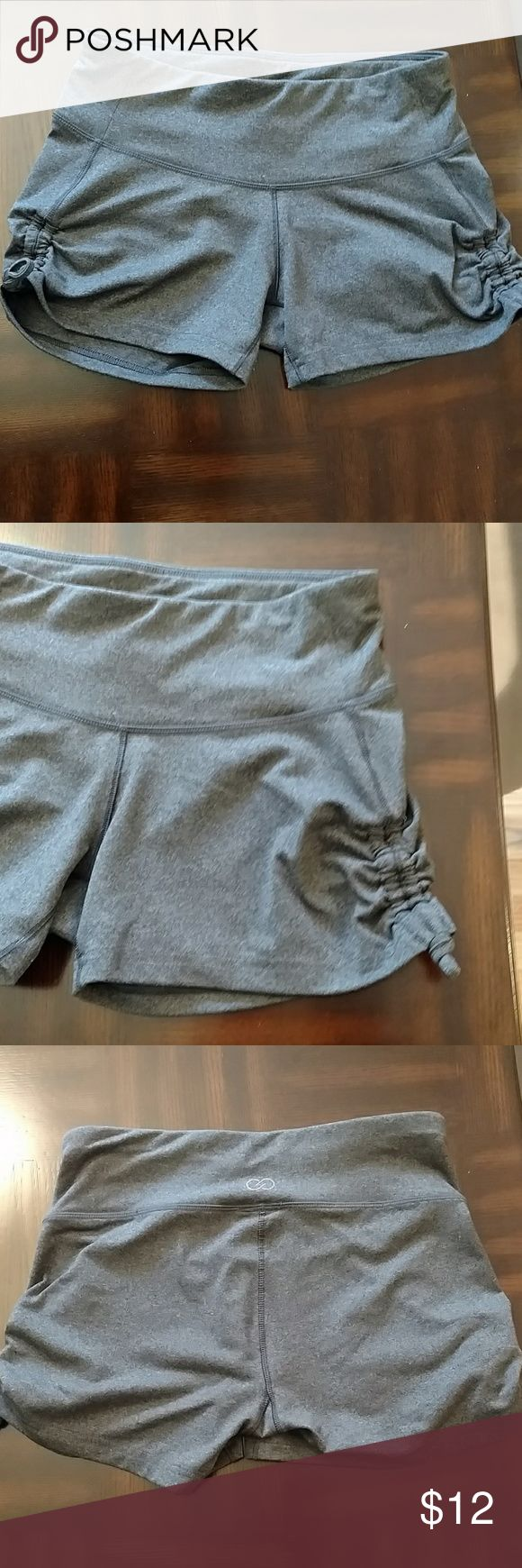 CALIA (by Carrie Underwood) Gray Athletic Shorts SUPER short (so high thigh area) Gray spandex​ material Really cute detail on the sides (you can't make the shorts shorter by pulling down the drawstring on the side!) CALIA by Carrie Underwood Shorts