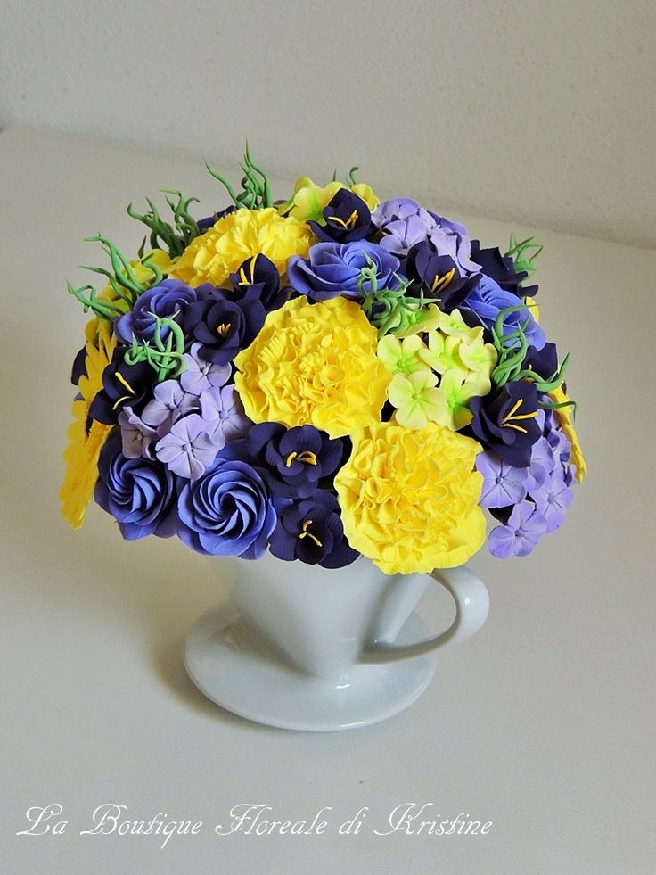 Una tazzina di fiori artigiano - Kristine Suibra Una tazzina di fiori che renderà la vostra casa ancora più allegra e colorata. L'abbinamento dei colori tra il giallo e il viola è perfetto. La composizione e composta dai garofani, le rose vittoriane, le gerbere, le fresie e le ortensie. I fiori e il verde sono fatti interamente a mano di argilla polimerica. L'altezza è di circa 20 cm (compreso la tazzina). Può essere realizzata in diversi colori su richiesta.