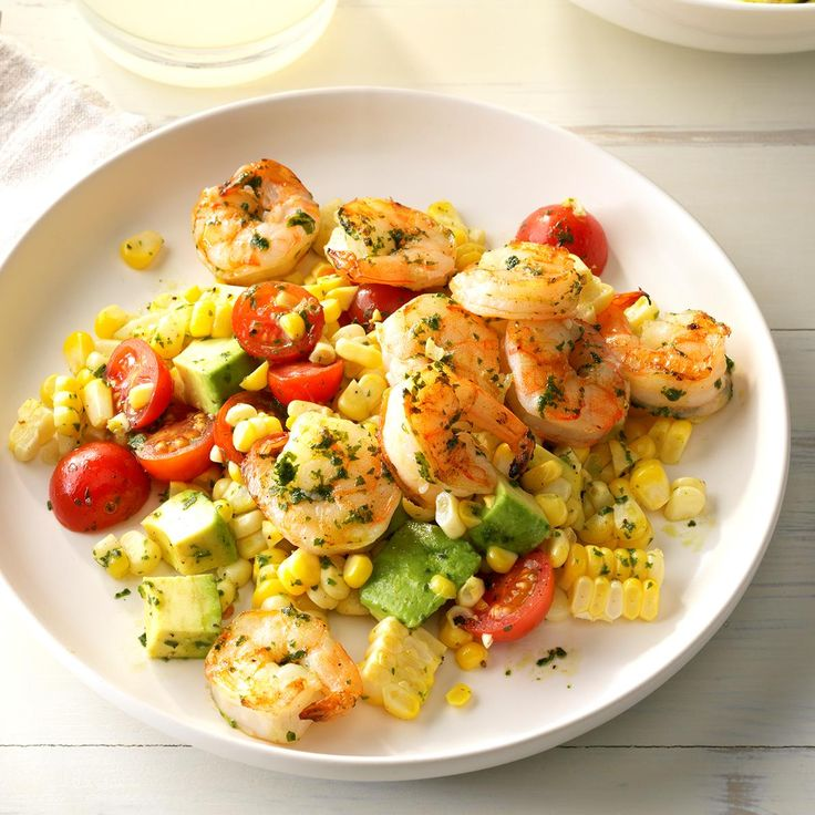 Pesto Corn Salad with Shrimp Recipe -This recipe showcases the beautiful bounty of summer with its fresh corn, tomatoes and delicious basil. Prevent browning by placing plastic wrap directly on the salad or spritzing with lemon juice. —Deena Bowen, Chico, California