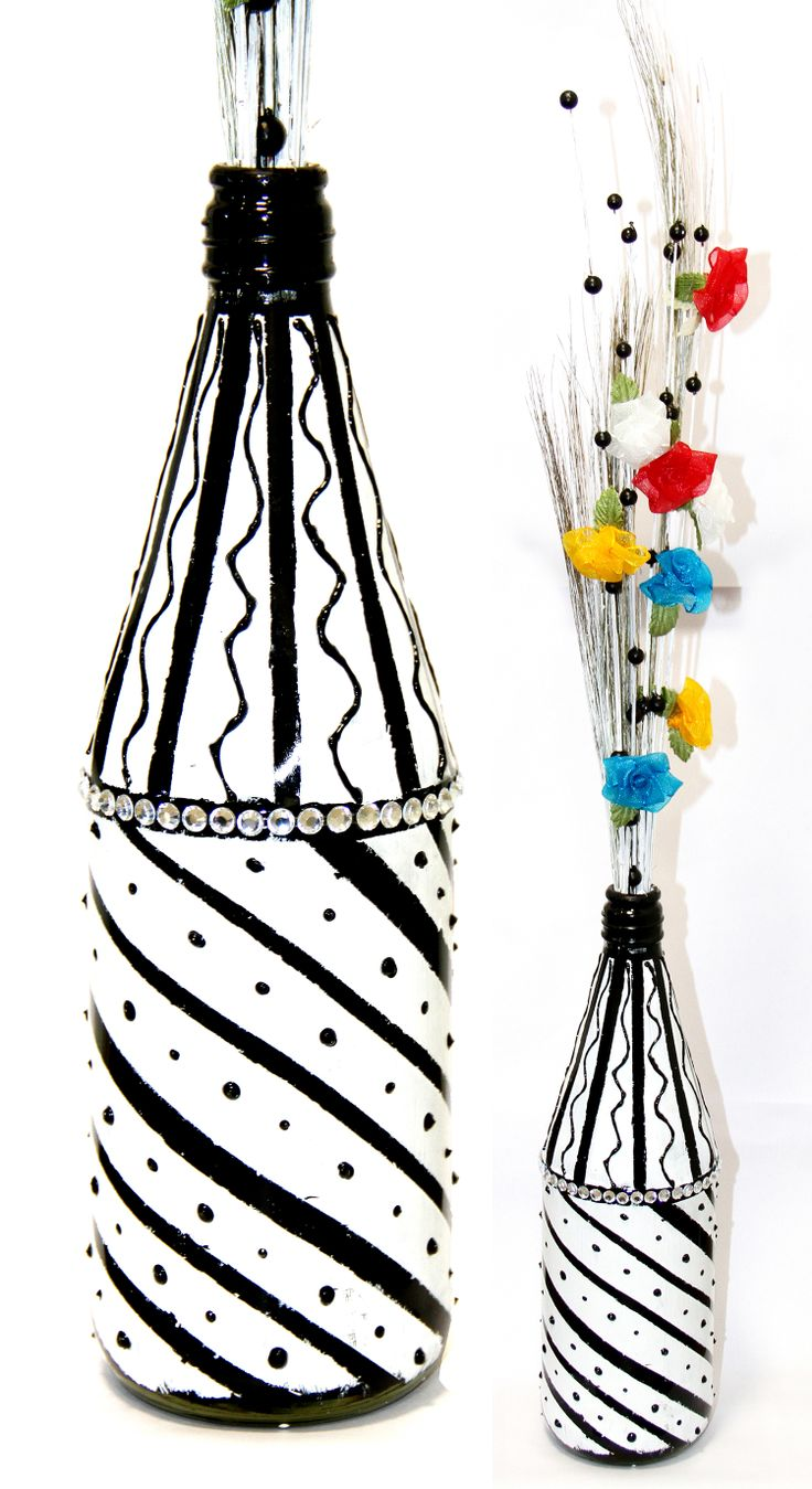 Flower vase made out of Empty sauce bottle with the broom sticks coloured in white with thermocol balls and few ribbon flowers.