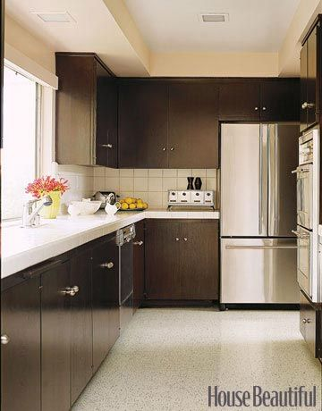 Designer Michael Berman laid a linoleum floor in the kitchen and stained the original walnut cabinets the color of black tea to set off the white tile of the countertops.