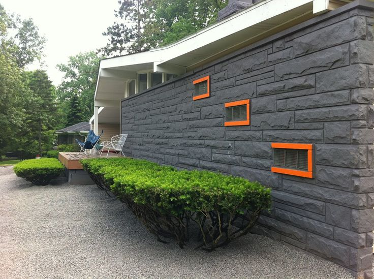 painted grey privacy wall with stylized boxwood bushes orange accents mcm exterior find this pin and more on mid century modern