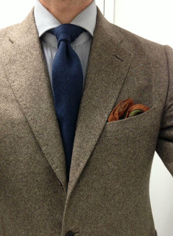 Light brown tweed jacket, white shirt with light grey pinstripes, navy tie