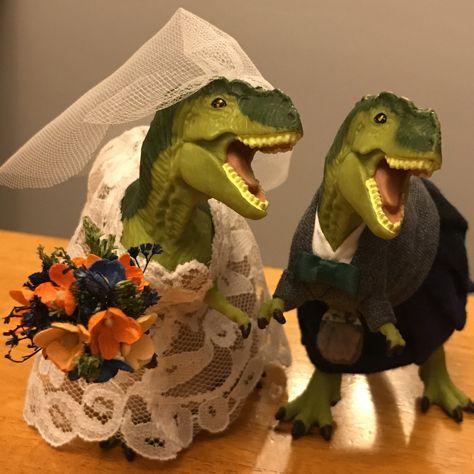Custom made dinosaur wedding cake topper.  Handmade lace wedding gown with miniature bouquet.  Groom is wearing a grey tweed jacket , tartan kilt and grey sporran. #weddingcaketopper #dinosaurwedding # dinosaur #trex #trexcaketopper #uniqueweddingcaketopper #animalcaketopper #bestcaketoper #dinosaurgroom #dinogroom #dinobride #dinosaurbride #jurassicwedding #dinosaurparty #museumwedding