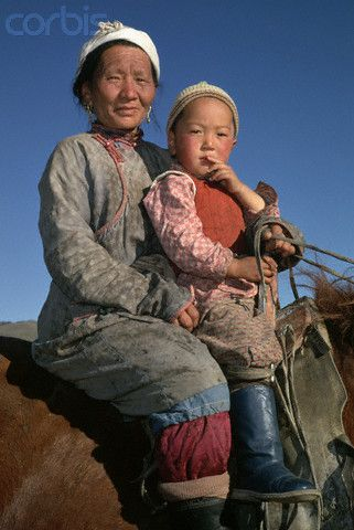 A woman with her young son ride a Mongolian horse on a grassy plain of rural Mongolia.  #world_cultures