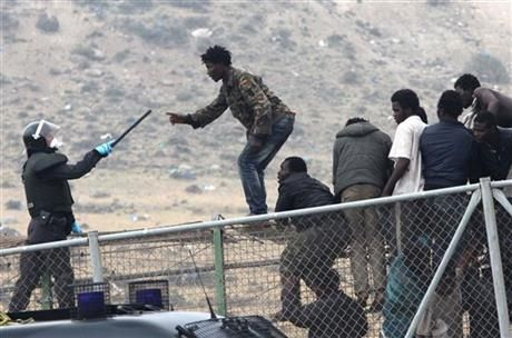 A sub-Saharan migrant agues with a Spanish Guardia Civil officer holding a baton, as they sit on top of a metallic fence that divides Morocco and the Spanish enclave of Melilla, Thursday, May 1, 2014. (AP Photo/Fernando Garcia) ▼1May2014AP|700 migrants rush at Spain's border, 140 breach it http://bigstory.ap.org/article/700-migrants-rush-spains-border-140-breach-it #Melilla