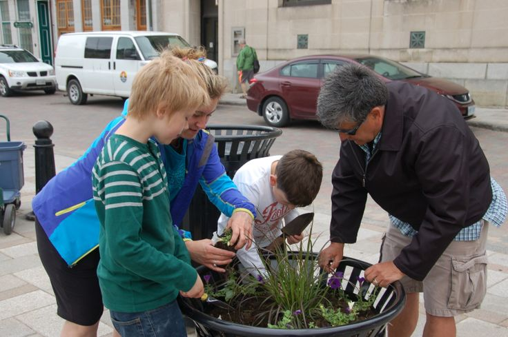 Dale Baker showing the children how to properly plant flowers at the 2014 Kingston Blooms Kick Off Event.