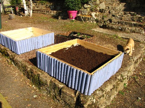 Potagers en carré, réalisés avec planches entourés de petites barrières de demi rondins en bois autoclave repeintes.