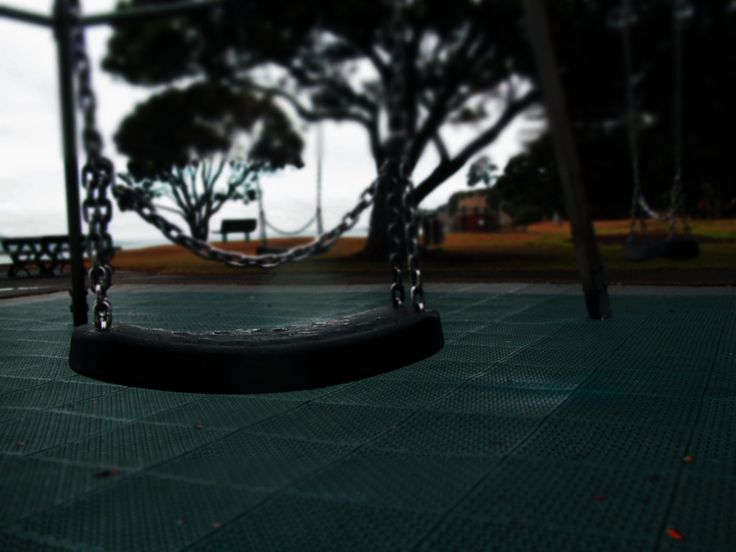 The swings in the playground at Browns Bay beach. In a creepy style filter. New Zealand