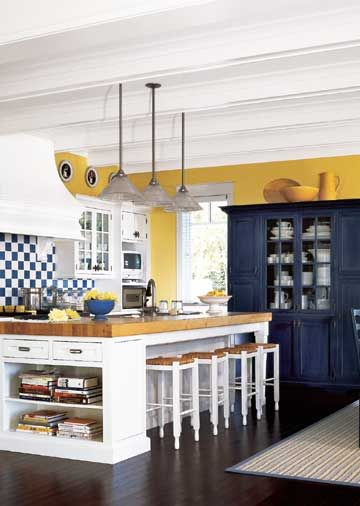 Cottage Modern- Open shelves at one end of this island are a handy place to keep cookbooks. Seating for four was arranged opposite the range with enough overhang so stools can be pushed underneath. The island is lit with three pendant lights overhead.