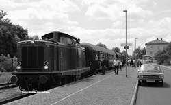 Das Rhönzügle, die Museumsbahn Mellrichstadt-Fladungen (für die ich keine Rubrik fand ?), bekam am 5.7.2014 Besuch von einem Sonderzug mit 2x DB V100. Es kamen dazu zwei hist. Garnituren von der Rennsteigbahn mit BR 213 sowie von Würzburg (DGEG) mit der V 100 1200. Die sehen wir hier mit einem 1970er Taxi und einem Setra-Bus im Hintergrund am Bahnhof von Mellrichstadt. An dem Wochenende waren die Fladungen Classics, das WE, an dem im ganzen Ort Fladungen die Zeit mindestens 40 Jahre zurück…