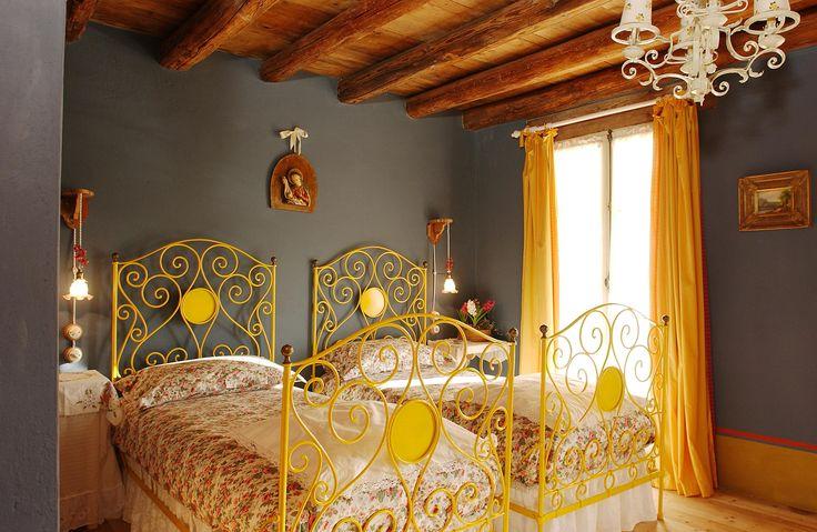 Stanza BLU, matrimoniale classica (o a due letti). Confortevole e luminosa, la stanza BLU si trova al primo piano ed è ricca di dettagli incantevoli, come il bel letto in ferro battuto dipinto di giallo. Grazie alle grandi finestre, su entrambi i lati, gode di una bella vista sul giardino e sul grande orto.