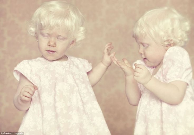Pretty in pink: Two little girls in matching dresses snapped in an action shot by Brazilian artist Gustavo Lacerda. Ridiculed-misunderstood-feared-magical-powers--Artist-s-poignant-pictures-sufferers-albinism.